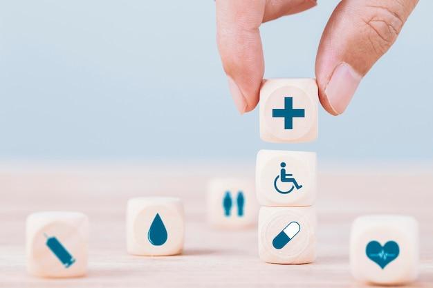 Рука выбирает символ здравоохранения иконы смайлика медицинский на деревянном блоке, концепции здравоохранения и медицинского страхования