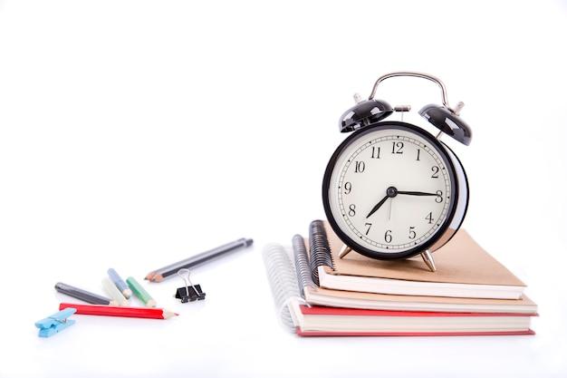 本の山と色付きのペンと白い背景の上の目覚まし時計
