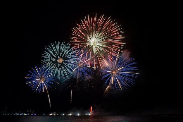 海のビーチでお祝いの美しいカラフルな花火大会