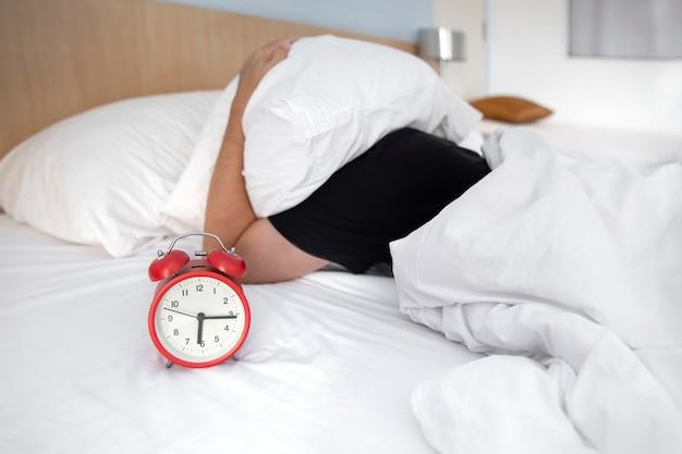 若い男性が寝室の枕の下で彼の頭を彼のベッドで寝ている間彼の目覚まし時計で強調しました。