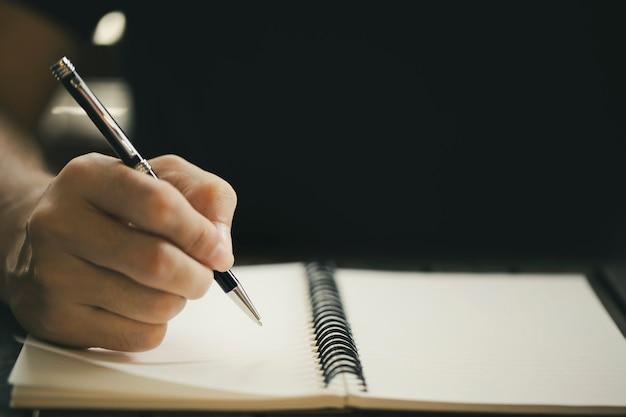 木製のテーブルの上のノートに書くペンを持つ男性の手のクローズアップ