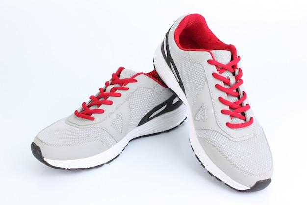 Серые кроссовки с красными кружевами на белом фоне