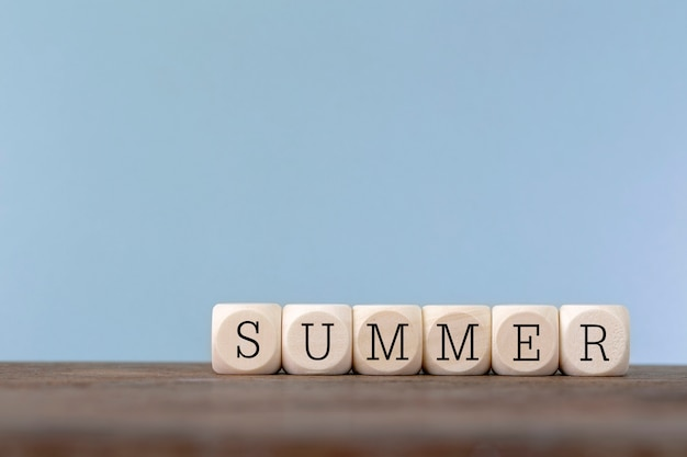 木製のテーブルに木製の立方体で書かれた夏の言葉