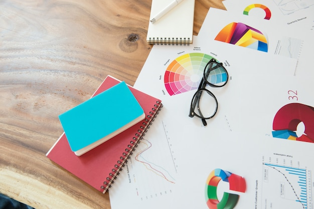 チャート、眼鏡ノート、木製の机の上にペンでビジネスマン職場。