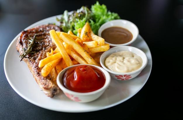 肉のグリル、ポークチョップステーキ、ペッパーソースとサラダ。