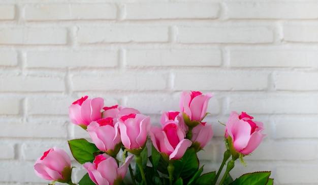 Букет роз на белой предпосылке кирпичной стены с космосом экземпляра.