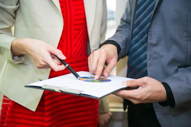 ビジネスの男性と働く女性は、紙のシートレポート、ビジネスコンセプトの仕事について話します。