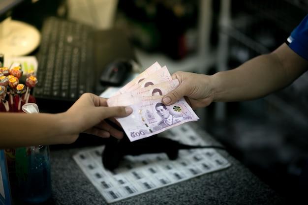 Наконсаван, таиланд. женщина расплачивается наличными с таиландскими банкнотами. тайские баты денег.