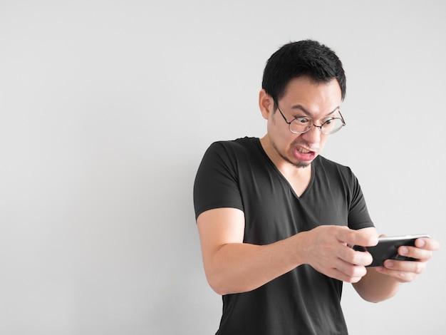 怒っているアジアの男がモバイルゲームを失っている。