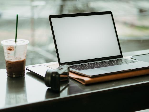 カフェのカメラと氷のコーヒーを持つ空の画面のラップトップ。