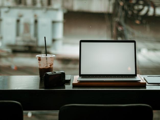 カフェでカメラと氷のコーヒーを持つ空のスクリーンラップトップ