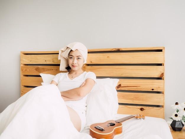 女性はベッドでウクレレを使ってリラックスした一日を過ごしています。