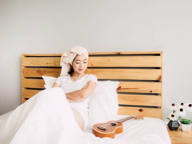 女性はベッドでウクレレでリラックスした一日を過ごしています。