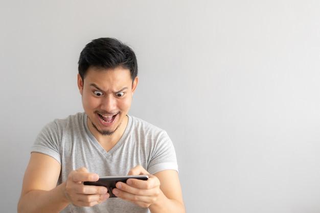 Сумасшедшее и смешное лицо человека, пристрастившегося к мобильной игре.