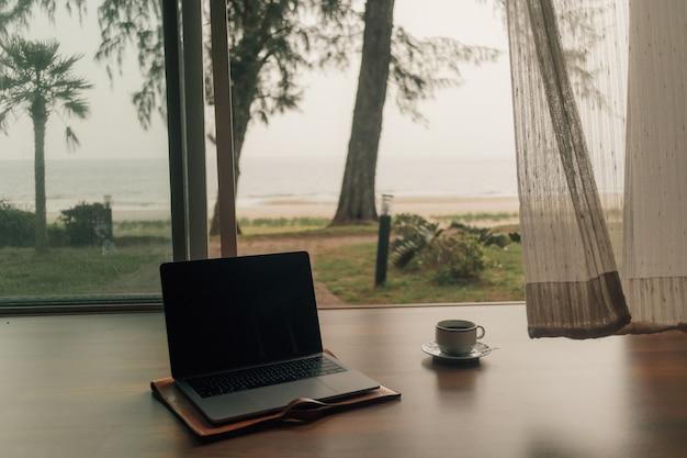 秋のビーチの眺めでドアのステップでラップトップとホットコーヒーカップ。