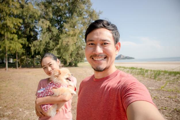 幸せなアジアカップルとビーチで子犬。