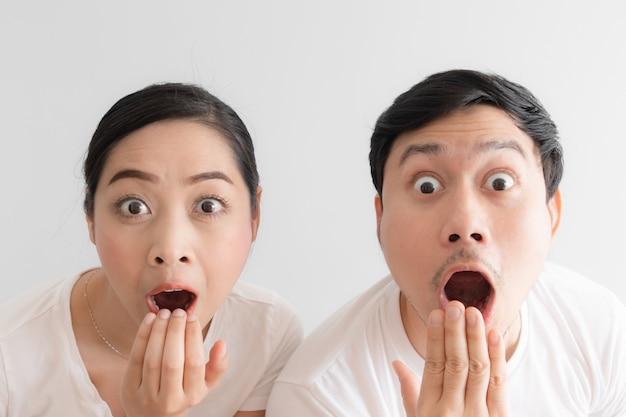 Удивлен над парой смешное лицо в белой футболке и белом фоне.