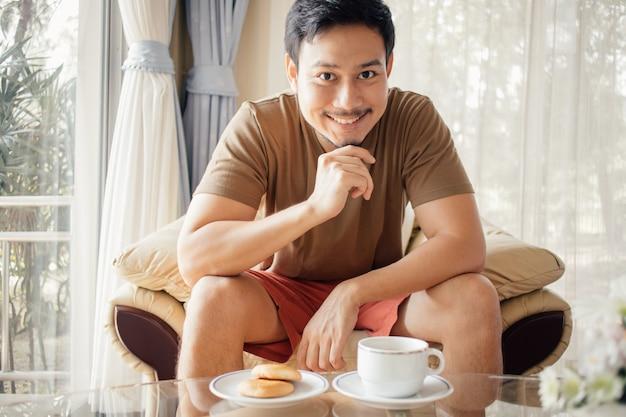 彼の朝食のコーヒーセットを持つ幸せなアジア人。