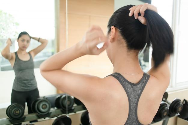 Азиатская женщина готовится к тренировке.