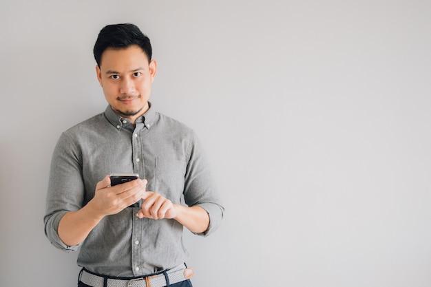 アジアのハンサムな男の幸せそうな笑顔は、灰色の背景に分離されたスマートフォンスタンドを使用します。