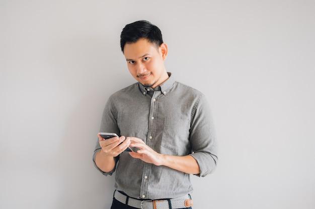 アジアのハンサムな男の幸せな笑顔の顔は灰色の背景に分離されたスマートフォンスタンドを使用します。