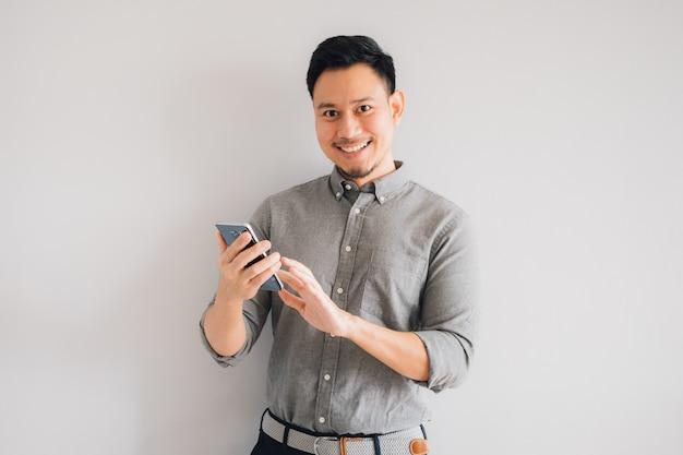 ハンサムなアジア人の幸せな笑顔の顔は、スマートフォンを使用します。