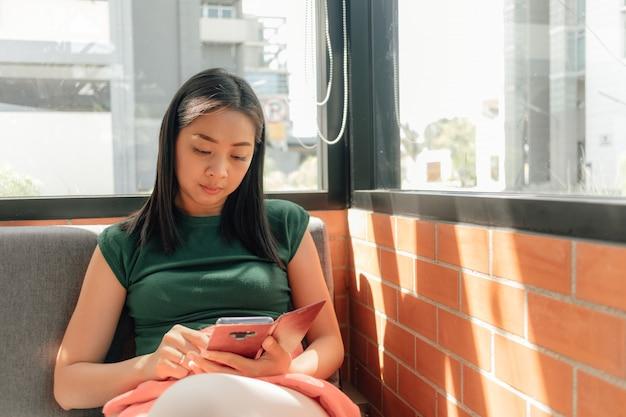 Женщина использует свой смартфон, телефон сидит в углу кафе