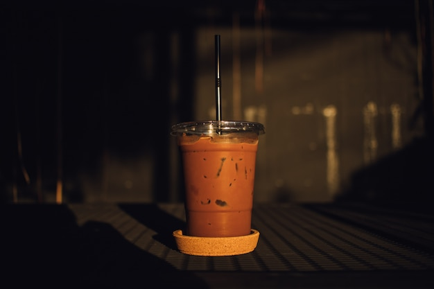 黒いテーブルの上のプラスチック製のガラスのアイスチョコレート。
