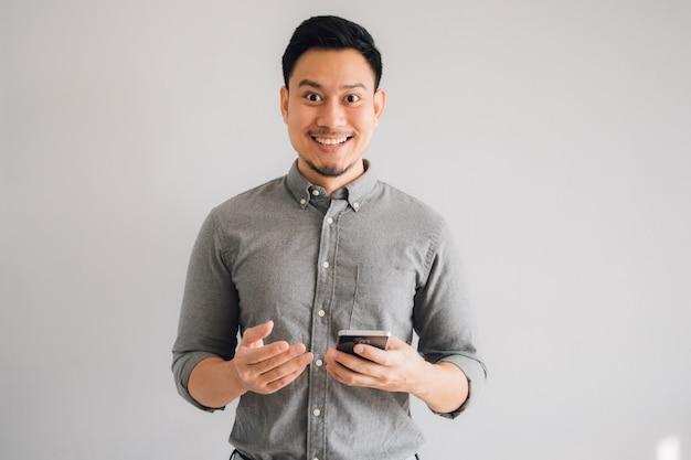 アジア人の幸せとすごい顔が孤立した灰色の背景にスマートフォンを使用します。