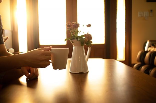 暖かな朝の光の中で一杯のコーヒー
