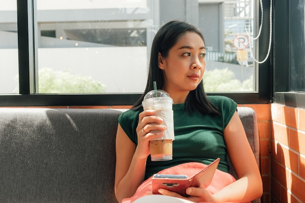 女性はアイスコーヒーを飲むと彼女のスマートフォンを使用します