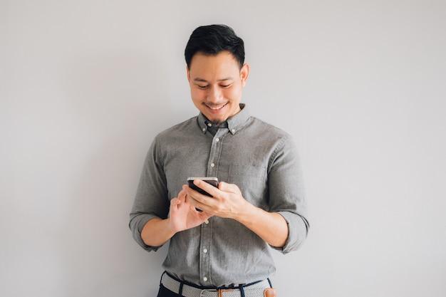 アジアのハンサムな男の幸せそうな笑顔は灰色の背景に分離されたスマートフォンスタンドを使用します。
