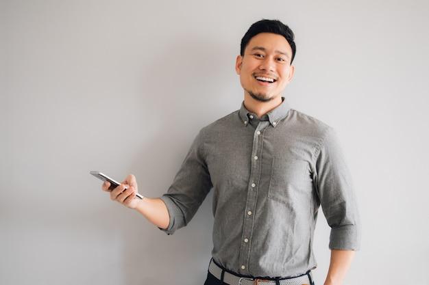 アジア人の幸せとすごい顔は、孤立した灰色の背景にスマートフォンを使用します。