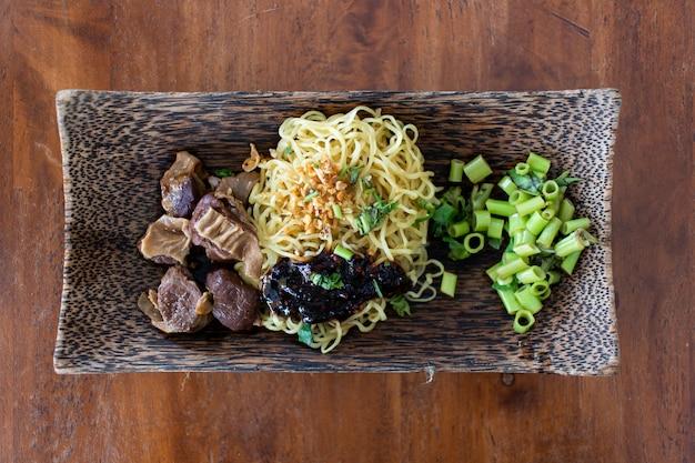 豚肉と醤油の卵麺は木製のボウルで提供しています。