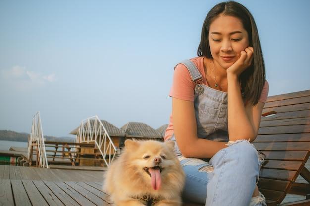 幸せなアジアの女性は彼女の犬と一緒にリラックスをお楽しみください。
