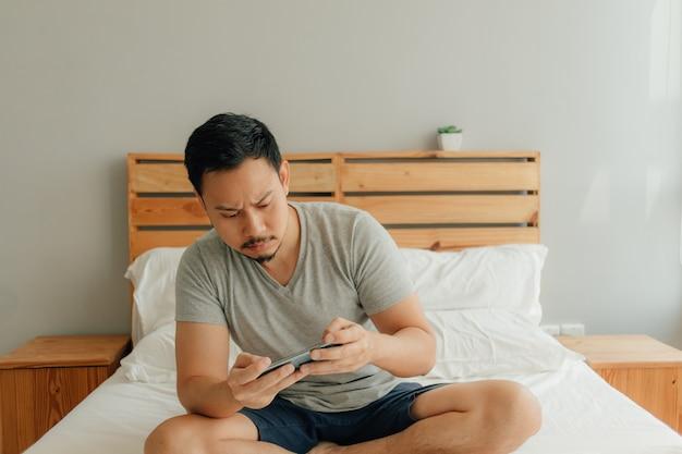 男は彼のスマートフォンをベッドの上にモバイルゲームをプレイしています。
