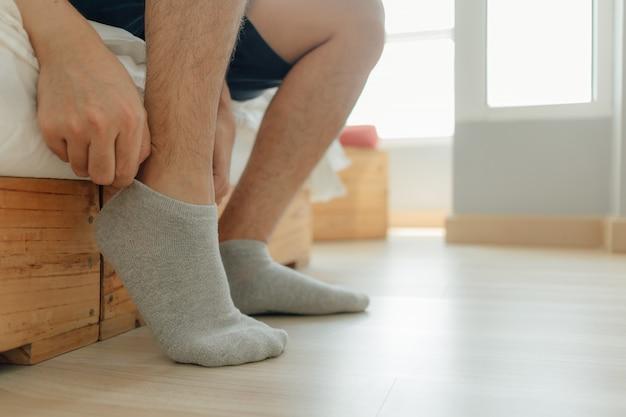 男は寝室で彼の足に靴下を履いています。準備と着飾るの概念。