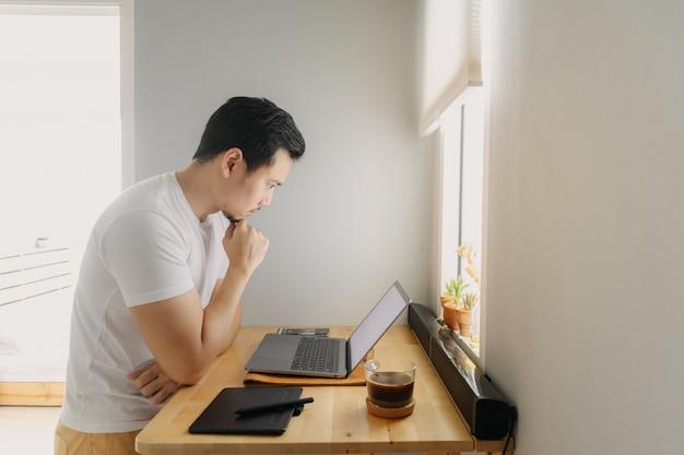 アジアのフリーランサーの男は考えていると彼のラップトップに取り組んでいます。フリーランスのクリエイティブ作品のコンセプトです。