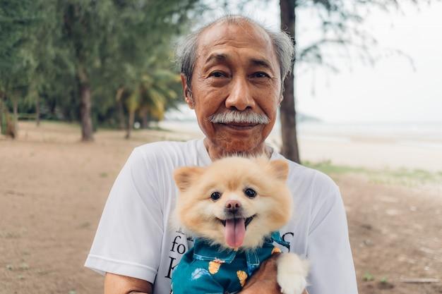 Дед держит поморскую собаку. концепция лучший друг старика.