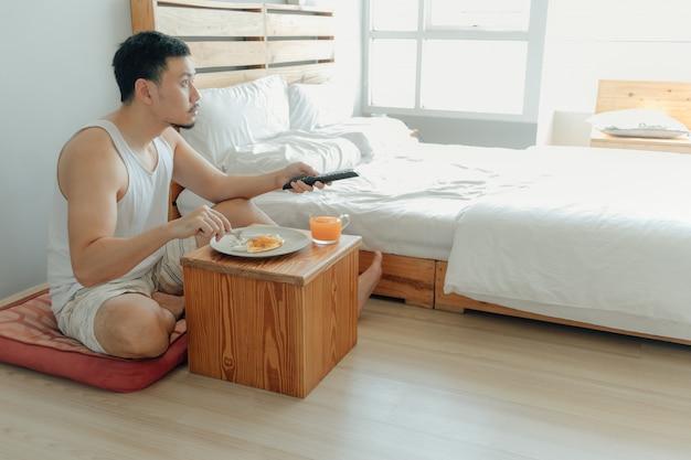 アジア人は朝食をとり、彼の寝室でテレビを見ています。