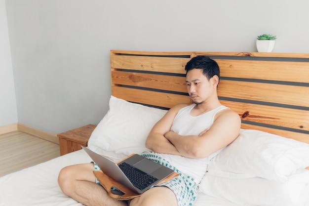 孤独な男は彼の居心地の良いベッドの上に彼のラップトップで働いています。フリーランサー仕事のライフスタイルのコンセプトです。