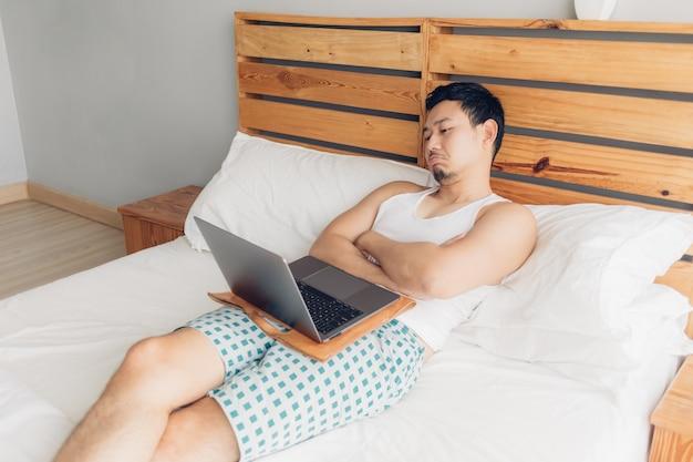 Сонный человек работает со своим ноутбуком на его уютной кровати. понятие о скучном образе жизни фрилансера.
