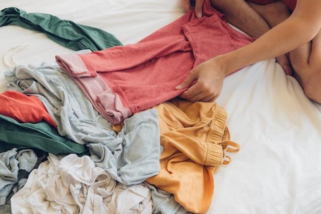 男はベッドの上で服を折って整理しています。