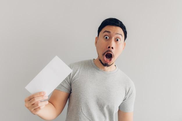 Человек шокирован и удивлен белым почтовым сообщением или счетом.