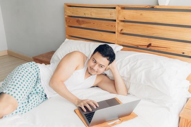 幸せな男は彼のベッドの上の彼のラップトップで働いています。フリーランサーの成功したライフスタイルのコンセプトです。