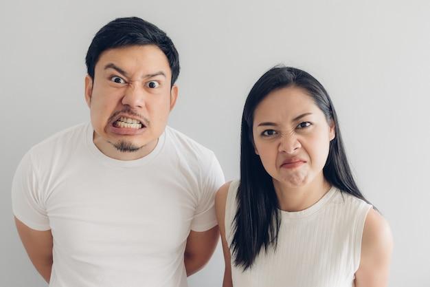 Сердитый любовник пар в белой футболке и серой предпосылке.