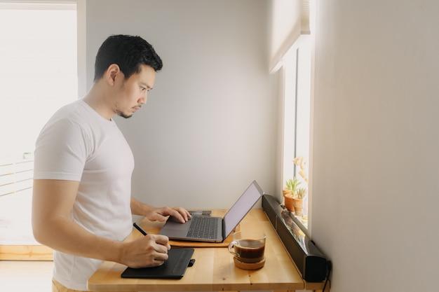 フリーランサーの男は彼のアパートで彼のラップトップに取り組んでいます。フリーランスのクリエイティブ作品のコンセプトです。