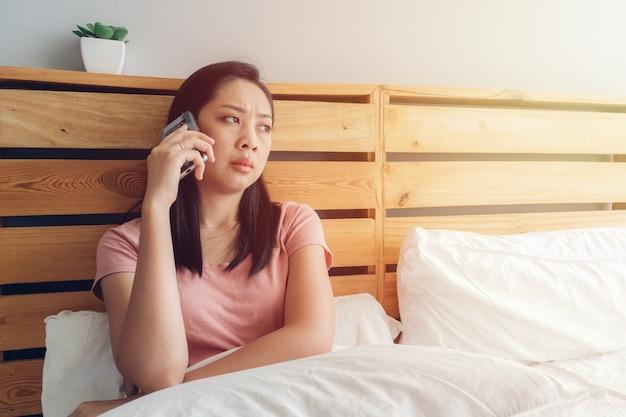 動揺している女性は彼女のベッドで電話で会話をしています。