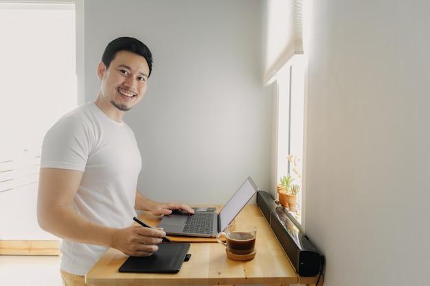 Счастливый фрилансер человек работает на своем ноутбуке.