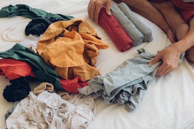 Человек складывает и расставляет одежду на кровати.